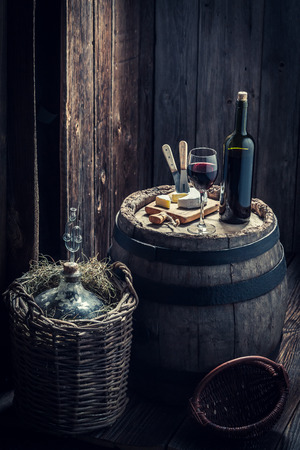 지하실에 치즈와 데미 존 (demijohn)이있는 레드 와인 스톡 콘텐츠