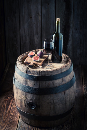 Fresh red wine and figs on oak barrel Фото со стока