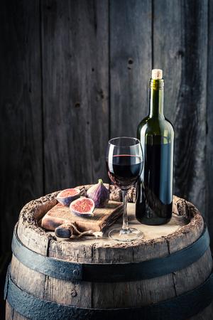 Fresh wine in glass with figs on oak barrel Stockfoto