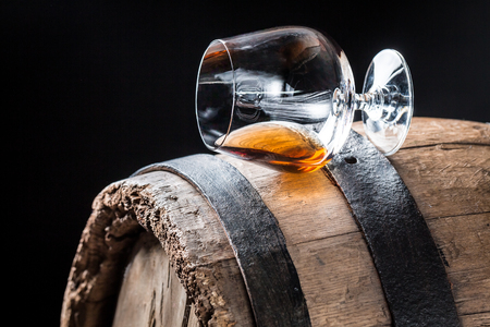Glass of good cognac on oak barrel Stock Photo