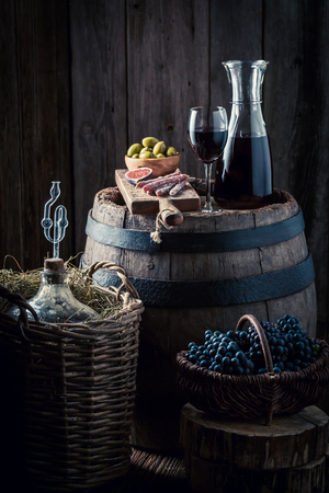 Wine in glass and red grapes in basement