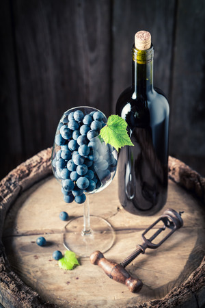Red wine in bottle and grapes in glass