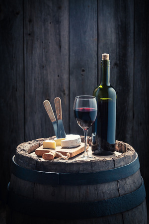 Red wine and camembert cheese on oak barrel Stock fotó
