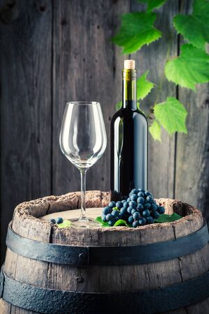 Red wine, empty glass and fresh grapes on old barrel
