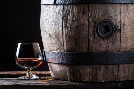 Glass of good brendy and oak barrel Stock Photo