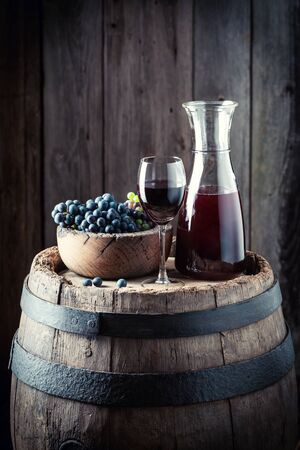 Red wine with fresh grapes on oak background