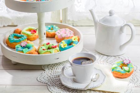 흰색 테이블에 커피와 함께 제공되는 화려하고 맛있는 도넛