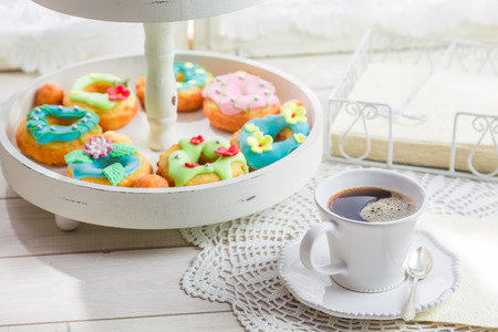 Coffee and donuts with colorful decoration on white table