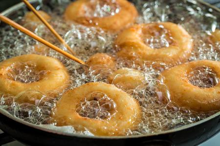 Zoete en smakelijke donuts bakken op verse olie