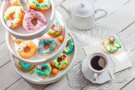 흰색 테이블에 커피와 함께 제공되는 맛있는 도넛