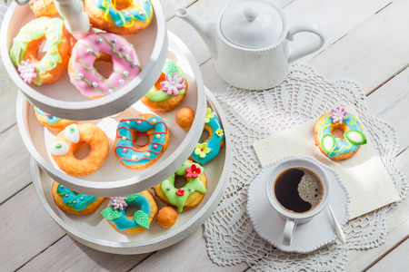 Delicious donuts served with coffee on white table
