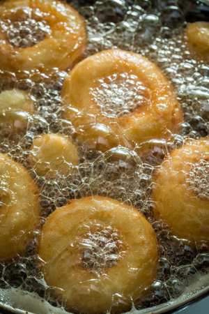Frying homemade and sweet donuts on hot oil Banco de Imagens