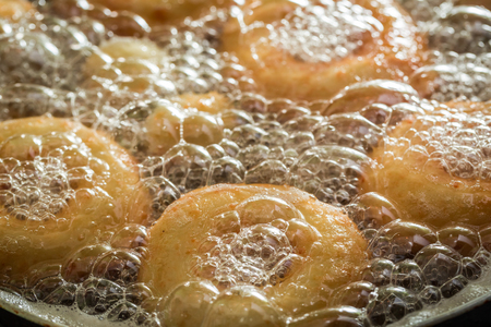 Frying tasty and homemade donuts on hot oil