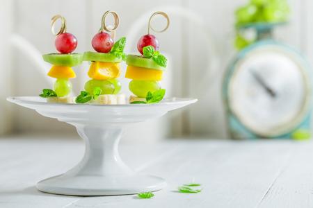 Smakelijke spiesjes met verschillende vruchten en munt op witte tafel Stockfoto