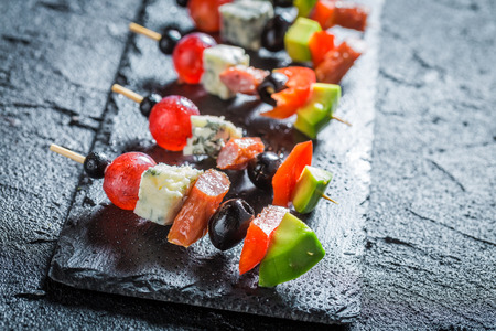 Various finger food with fresh ingredients on black rock Reklamní fotografie - 81965238