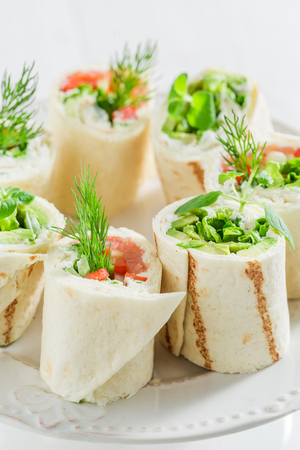 Tasty tortilla with salmon, cheese and vegetables on white table