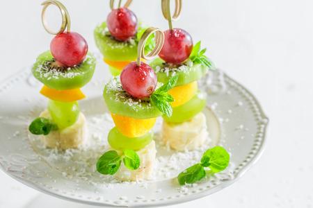 Zelfgemaakte spiesjes met fruit en munt op witte tafel