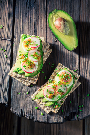 Tasty sandwich with avocado, eggs and radish on wooden table
