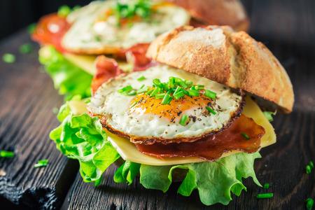 Close-up van heerlijke hamburger met sla, spek en eieren