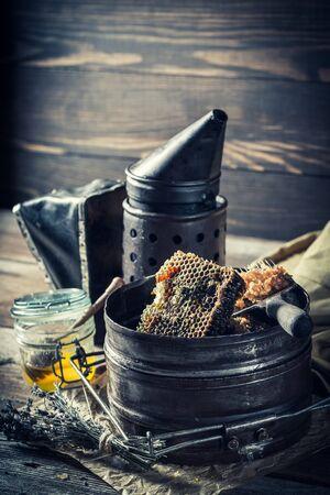 Roestige imkerhulpmiddelen met verse en zoete honing
