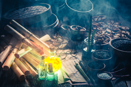 Old scrolls and recipe in magical kitchen laboratory Stock Photo