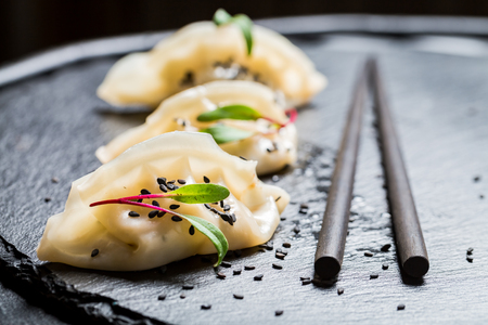 Closeup of hot gyoza dumplings on black rock Stock Photo