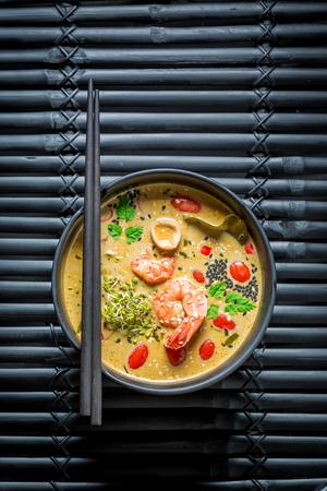 Tom Yum soup with chopsticks on black rock Stock Photo