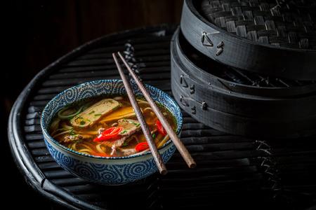 Tasty Thai broth with chopsticks on black background