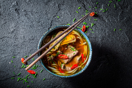 Red Curry soup with chopsticks on black table