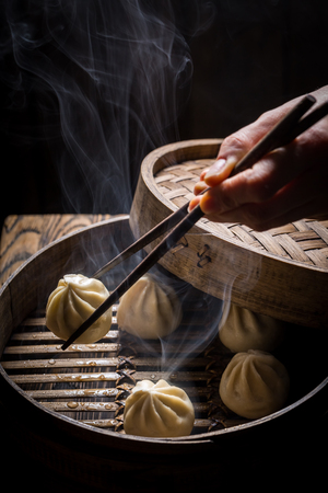 Hot chinese dumplings in wooden steamer on black background