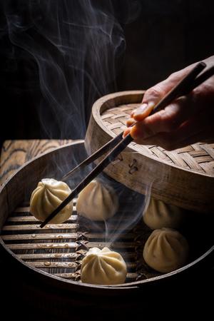 Hete Chinese bollen in houten stoomboot op zwarte achtergrond