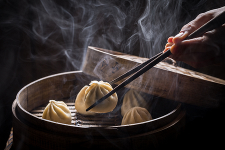Boiled and hot chinese dumplings on black background