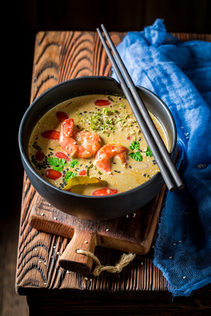 Closeup of delicious Tom Yum soup in black bowl