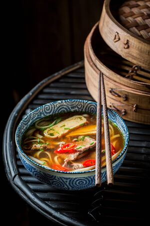 Tasty Thai broth with beef and noodle on black background