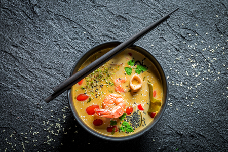 Closeup of Tom Yum soup with coconut milk and shrimps