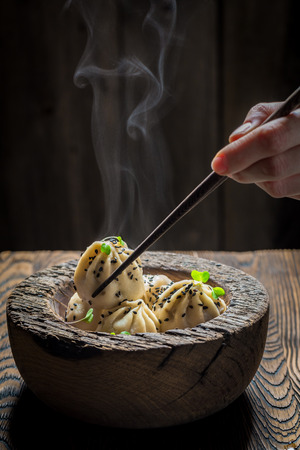 Closeup of chinese dumplings in wooden bowl on black background