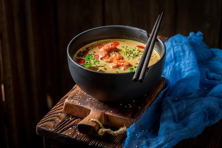 Closeup of hot Tom Yum soup in black bowl