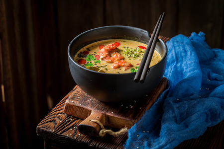 Closeup of hot Tom Yum soup in black bowl