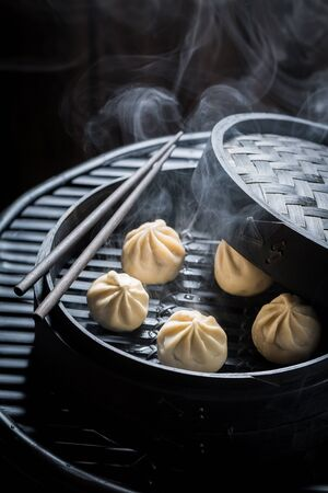 Manti dumplings in bamboo steamer on black background