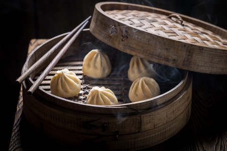 Fresh manti dumplings in bamboo steamer on black background