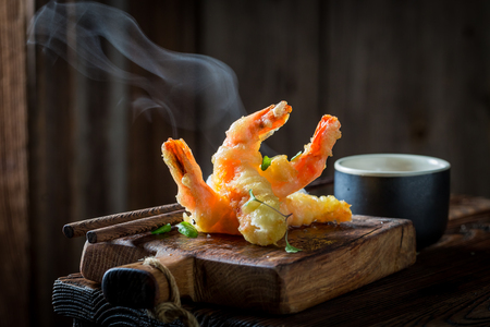 Tasty shrimp in tempura with red sauce on black background Foto de archivo