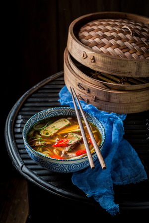 Tasty Thai broth in black bowl on black background