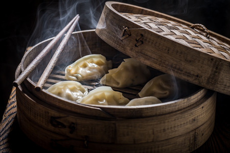 Closeup of hot gyoza dumplings in wooden steamer Stock Photo