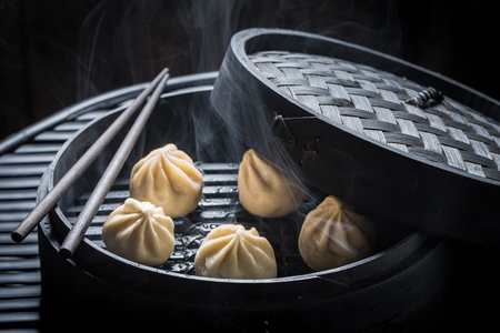 Closeup of manti dumplings in wooden steamer ob black background
