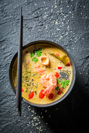 Tom Yum soup with shrimps on black rock Stock Photo - 84735919