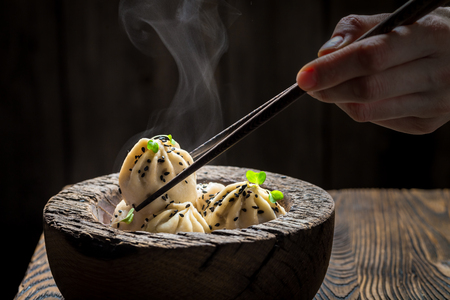 Closeup of homemade chinese dumplings in wooden bowl Stock Photo