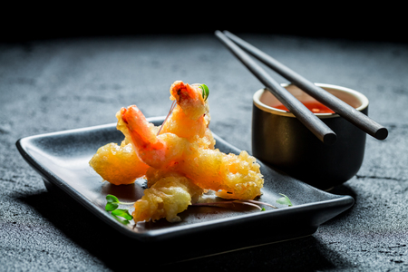 Hot shrimp in tempura with red sauce on black rock Stock Photo