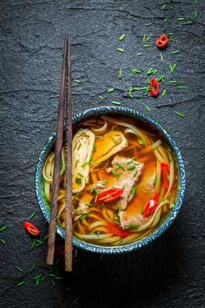 Enjoy your Red Curry soup with chopsticks on black rock