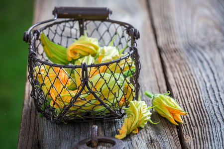 Fresh zucchini flowers on old wooden table