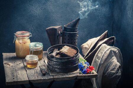 ハニカム構造体、帽子と蜂蜜とさびた養蜂家ツール 写真素材